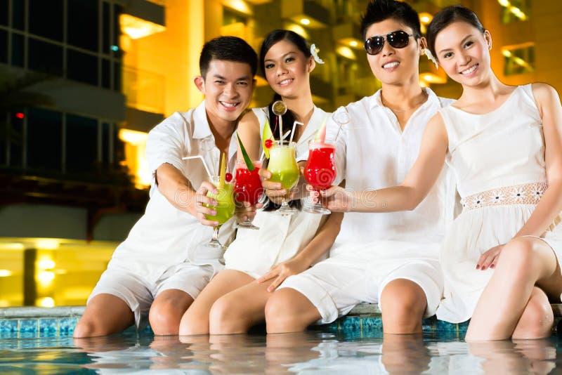 Pares chinos que beben los cócteles en barra de la piscina del hotel foto de archivo