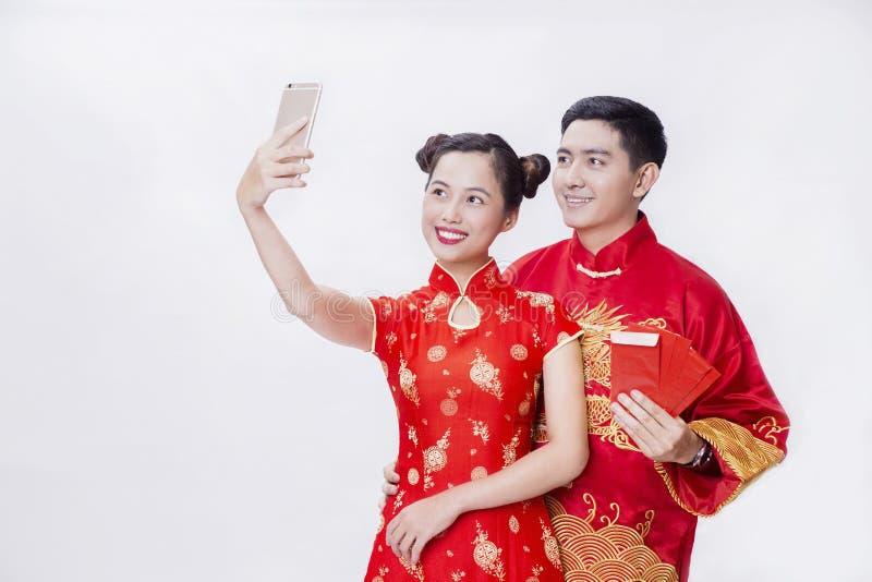 Pares chinos que llevan a cabo el artículo de la buena suerte por Año Nuevo foto de archivo libre de regalías