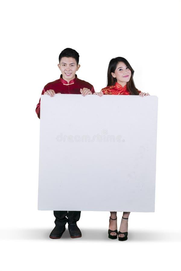 Pares chinos que sostienen un whiteboard en blanco imagen de archivo
