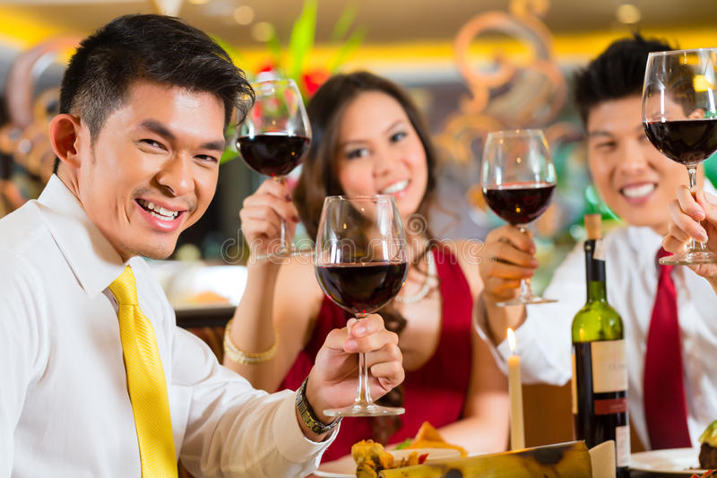 Pares chinos que tuestan con el vino en restaurante imagen de archivo