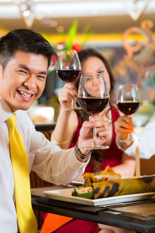 Pares chinos que tuestan con el vino en restaurante imagen de archivo libre de regalías