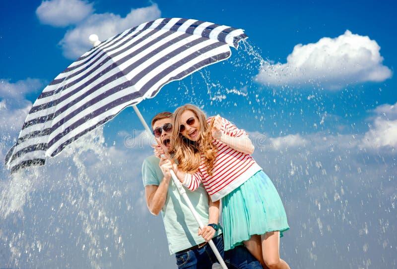 Pares chocados debajo del paraguas debido al clima tempestuoso imagenes de archivo