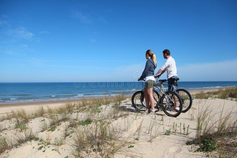 Pares com as bicicletas na praia imagem de stock royalty free