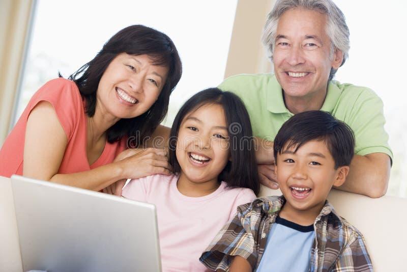 Pares com as duas crianças no quarto com portátil fotos de stock