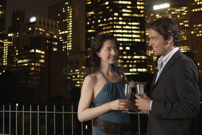 Pares com as flautas de champanhe contra a arquitectura da cidade na noite imagem de stock royalty free