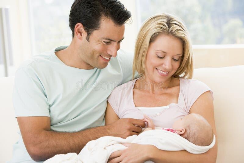 Pares com bebê novo em casa foto de stock royalty free