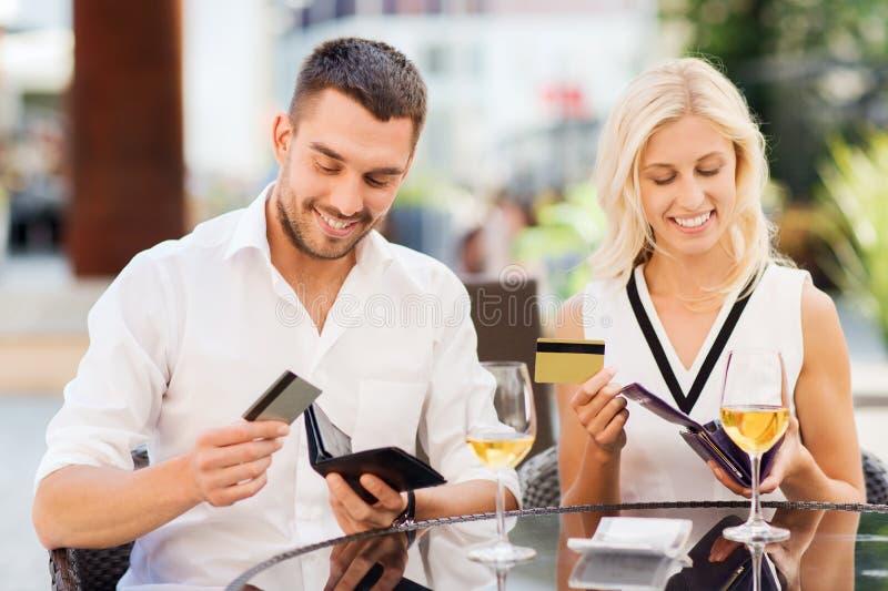 Pares com conta pagando de cartões de crédito no restaurante fotografia de stock