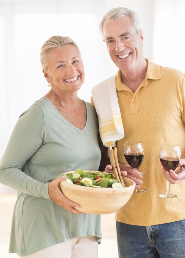 Pares com copo de vinho e salada vermelhos em casa foto de stock royalty free