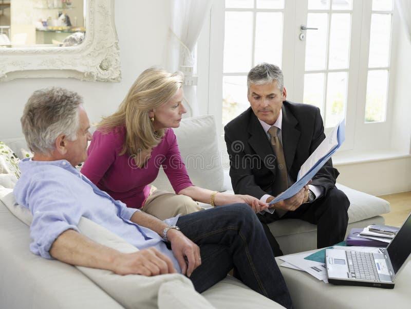 Pares com o conselheiro financeiro no sofá imagens de stock royalty free