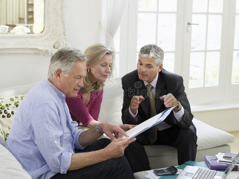Pares com o conselheiro financeiro no sofá foto de stock royalty free