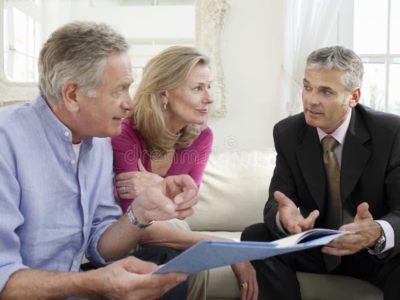 Pares com o conselheiro financeiro no sofá fotografia de stock royalty free