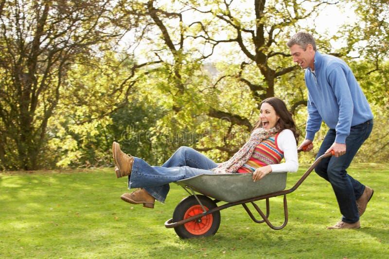 Pares com o homem que dá o passeio da mulher no Wheelbarrow fotos de stock royalty free