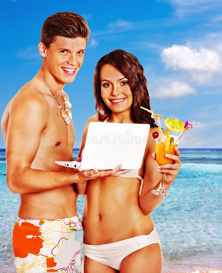 Pares com o portátil na praia imagens de stock royalty free