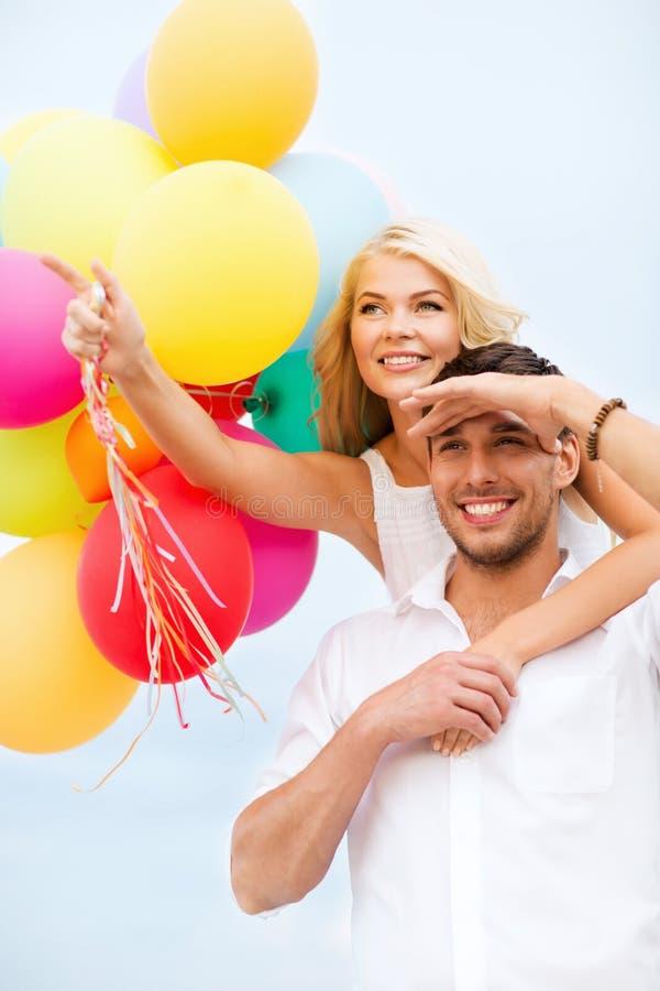 Pares com os balões coloridos no beira-mar imagens de stock royalty free