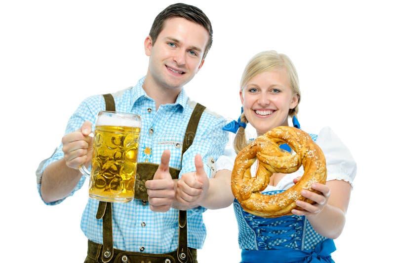 Pares com os canecos de cerveja e o pretzel da cerveja de Oktoberfest imagens de stock