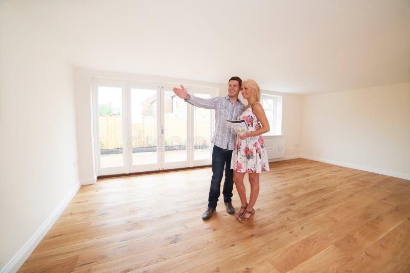Pares com os detalhes da propriedade que olham em torno da casa nova imagens de stock royalty free