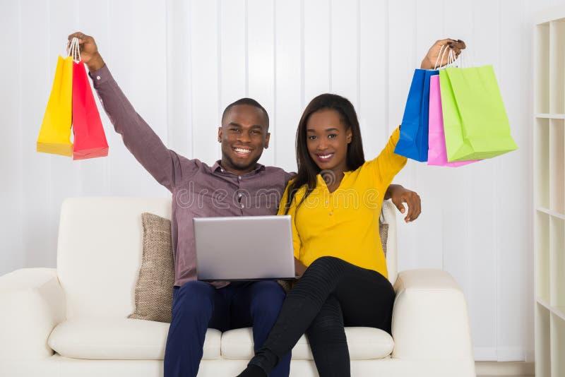 Pares com os sacos de compras e o portátil que sentam-se no sofá foto de stock royalty free