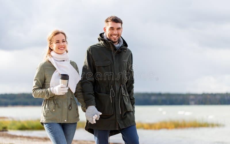 Pares com a secadora de roupa que anda ao longo da praia do outono fotografia de stock