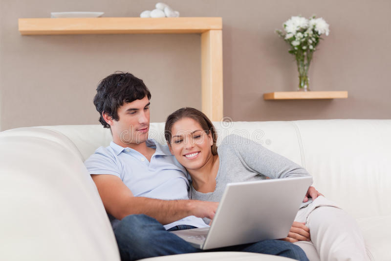 Pares com seu portátil no sofá imagens de stock