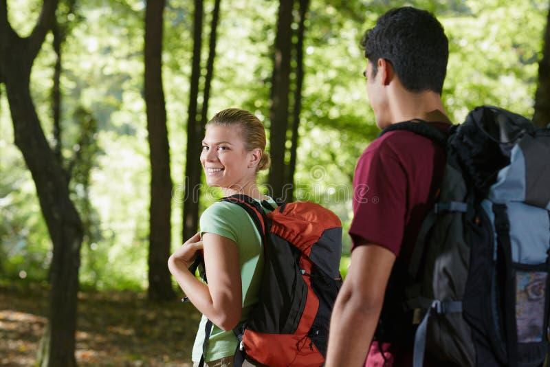 Pares com a trouxa que faz trekking na madeira fotografia de stock royalty free
