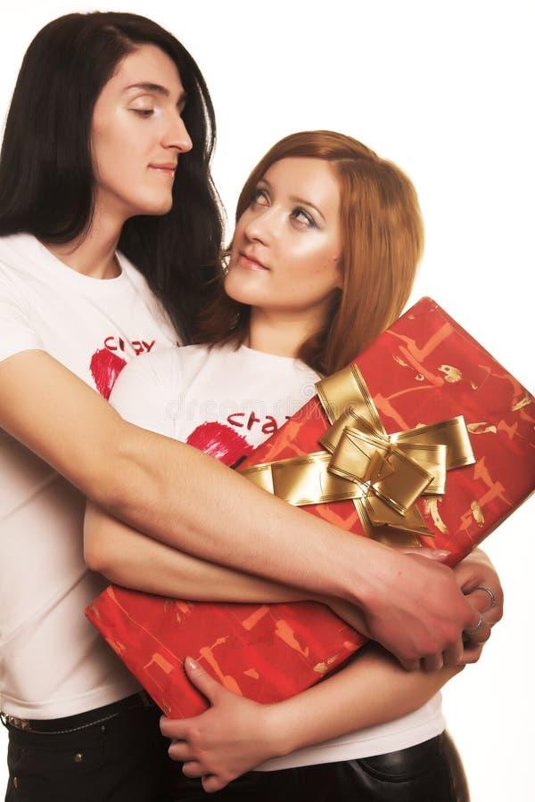 Pares com um presente sobre um fundo branco fotos de stock royalty free