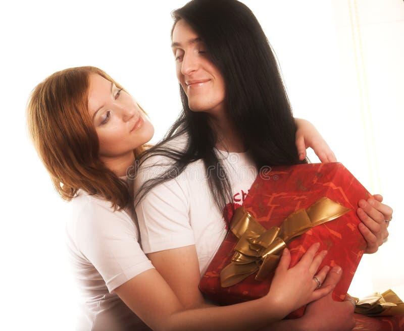 Pares com um presente sobre um fundo branco imagens de stock royalty free