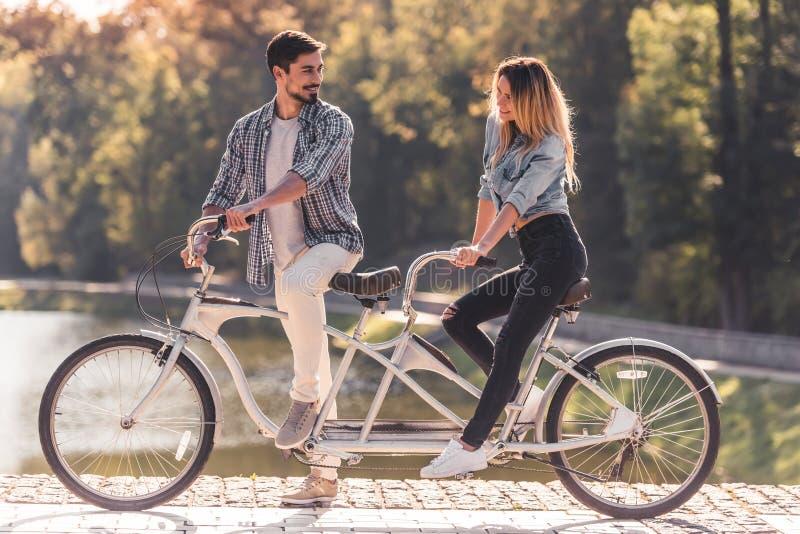 Pares com uma bicicleta em tandem imagem de stock