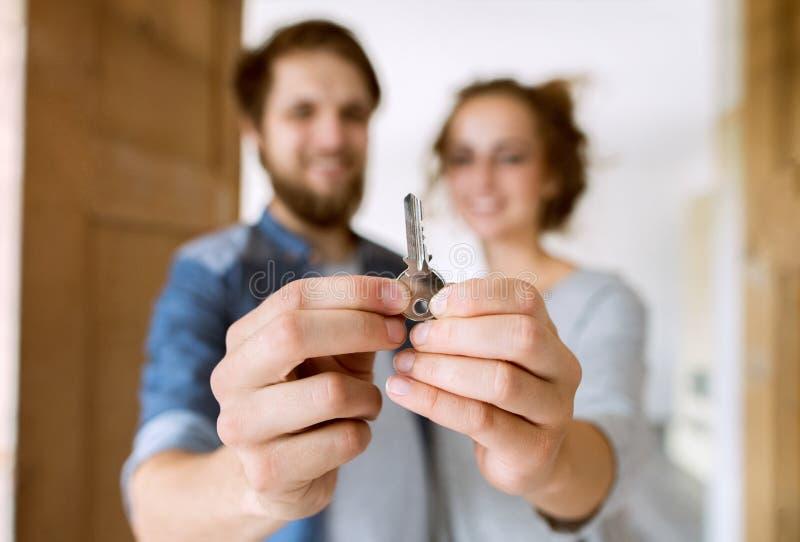 Pares com uma chave que move-se em sua casa nova fotografia de stock royalty free