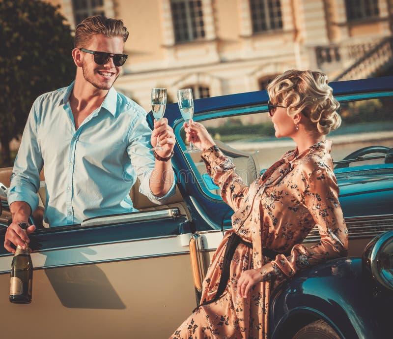 Pares con champán cerca del coche clásico fotografía de archivo libre de regalías