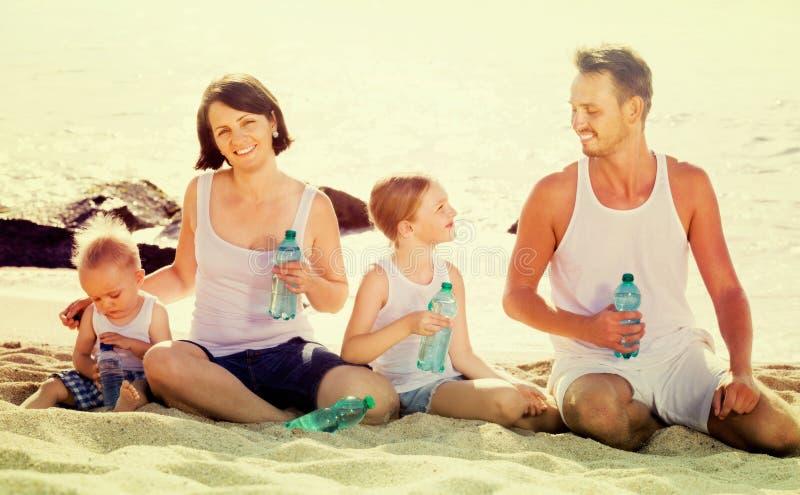 Pares con dos niños que beben el agua dulce en la playa arenosa imágenes de archivo libres de regalías