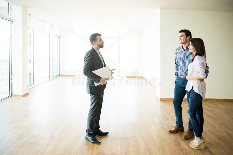 Pares con el agente inmobiliario Visiting New House foto de archivo