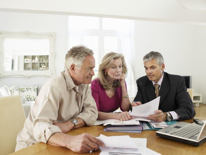 Pares con el consejero financiero en la tabla foto de archivo