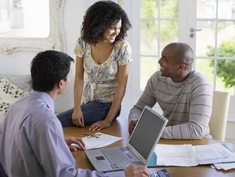Pares con el consejero financiero en la tabla imagen de archivo