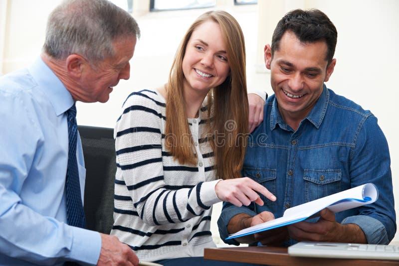 Pares con el consejero financiero que estudia el documento en oficina fotos de archivo