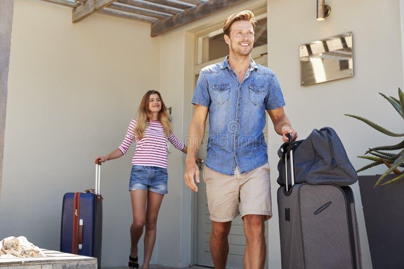 Pares con el equipaje que sale de la casa para las vacaciones imagen de archivo libre de regalías