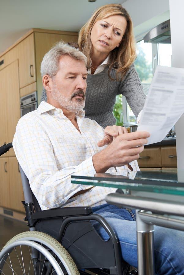Pares con el marido en letra de la lectura de la silla de ruedas imagen de archivo libre de regalías