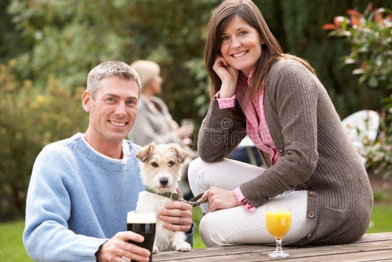 Pares con el perro de animal doméstico al aire libre que disfruta de la bebida en Pub imagenes de archivo