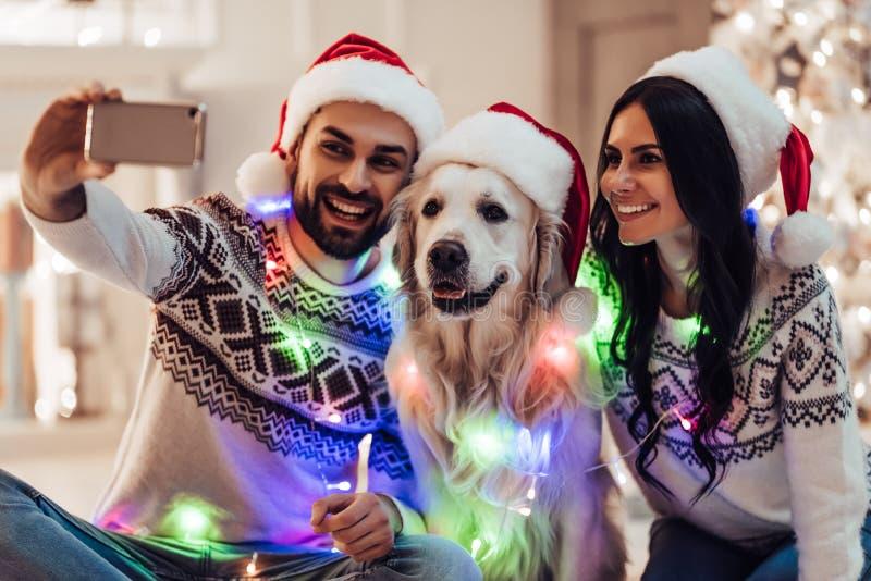 Pares con el perro en el ` s Eve del Año Nuevo imagenes de archivo