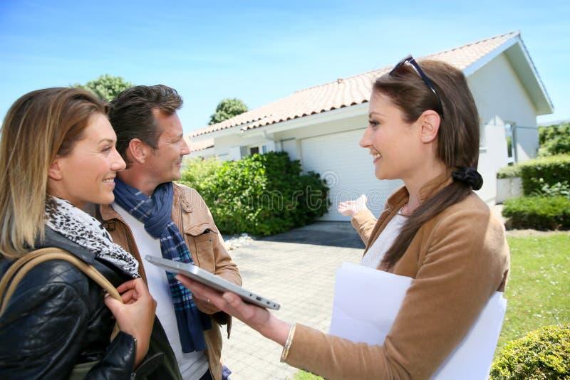 Pares con la casa futura que visita del agente inmobiliario foto de archivo