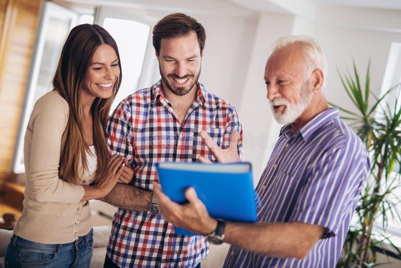 Pares con la casa que visita del agente inmobiliario mayor para la venta fotografía de archivo