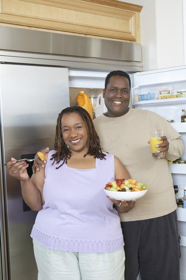 Pares con la comida y bebida por el refrigerador abierto imágenes de archivo libres de regalías