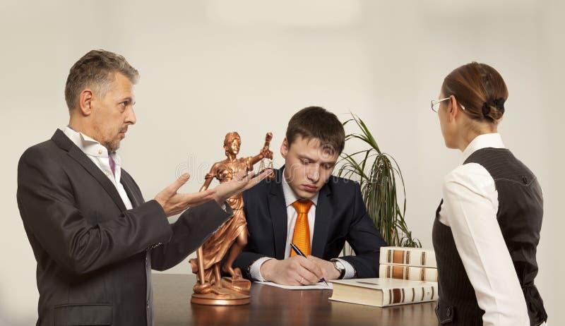 Pares con la escritura del juez en el escritorio ante el tribunal imagen de archivo libre de regalías