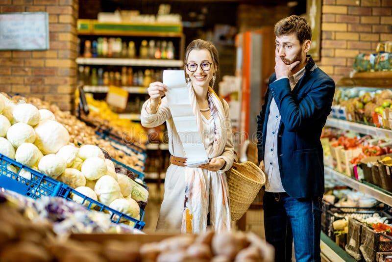 Pares con la lista que hace compras larga en el supermercado fotos de archivo