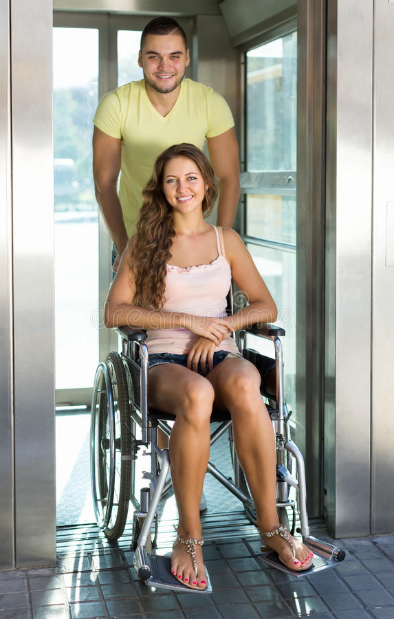 Pares con la silla de ruedas en elevador fotografía de archivo
