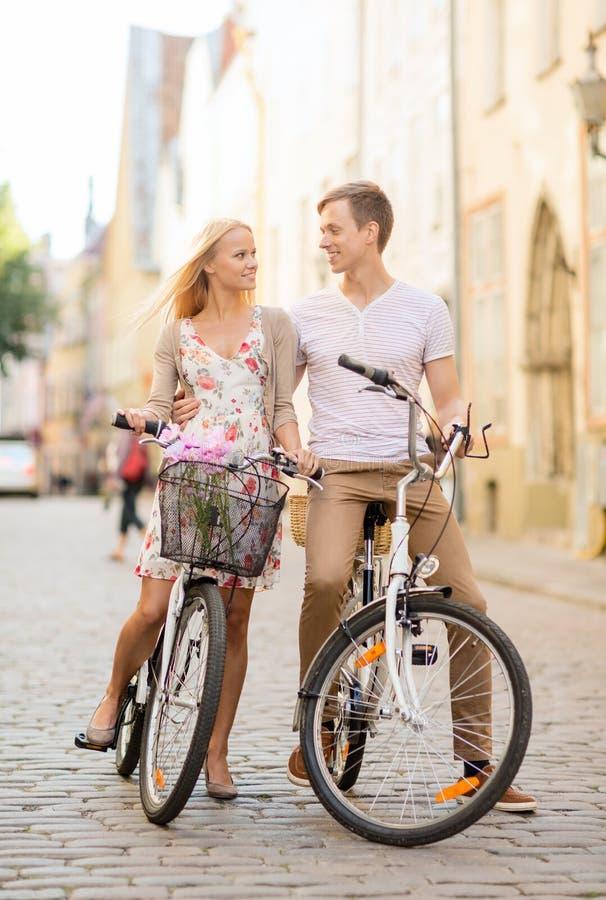 Pares con las bicicletas en la ciudad foto de archivo libre de regalías