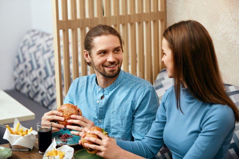 Pares con las hamburguesas en café foto de archivo
