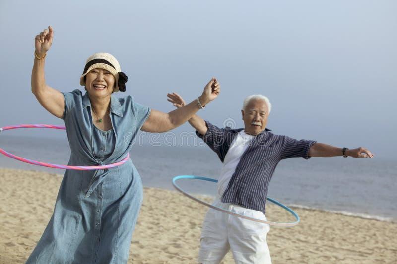 Pares con los aros del hula en la playa imagenes de archivo