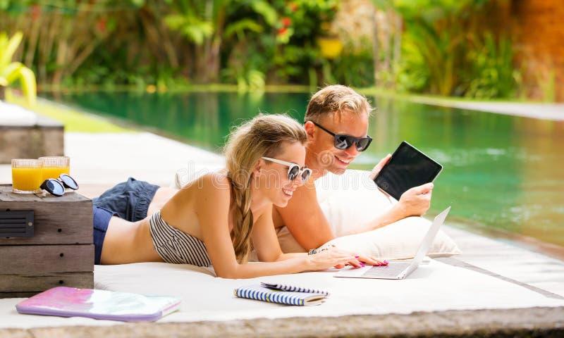 Pares con los ordenadores que se relajan en sofá por la piscina fotos de archivo libres de regalías