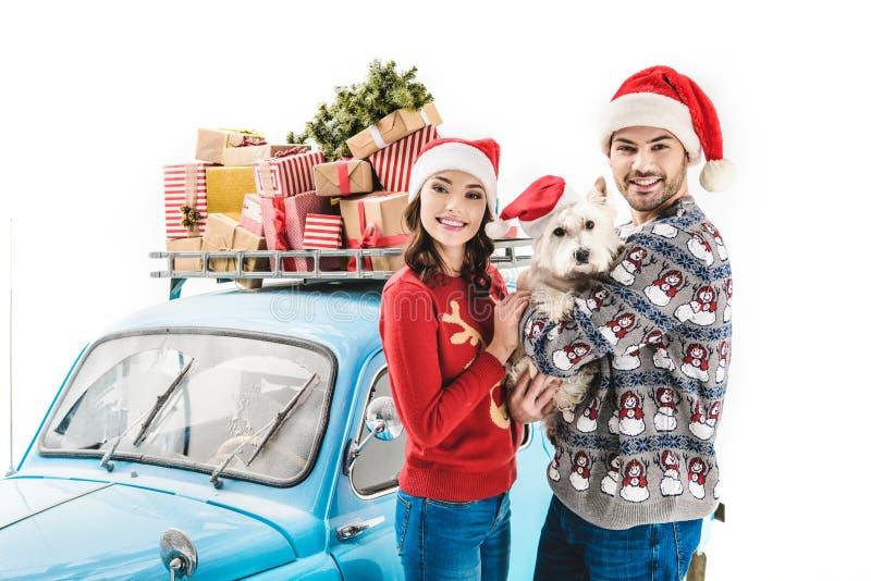 Pares con los regalos del perro y de la Navidad en el coche imagen de archivo