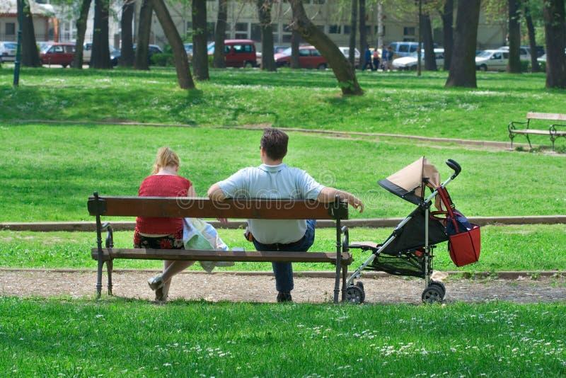 Pares con un carro de bebé que se reclina en el parque imagen de archivo